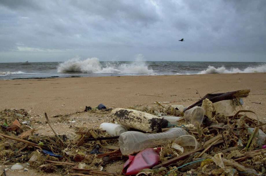 In this Aug. 13, 2015 photo, a plastic bottle lies among other debris washed ashore on the Indian Ocean beach in Uswetakeiyawa, north of Colombo, Sri Lanka. For years along the Cornish coast of Britain, Atlantic Ocean currents have carried thousands of Lego pieces onto the beaches. In Kenya, cheap flip-flop sandals are churned relentlessly in the Indian Ocean surf, until finally being spit out onto the sand. In Bangladesh, fishermen are haunted by floating corpses that the Bay of Bengal sometimes puts in their path. And now, perhaps, the oceans have revealed something else: parts of Malaysian Airlines Flight 370, the jetliner that vanished 17 months ago with 239 people on board. (AP Photo/Gemunu Amarasinghe) Photo: Gemunu Amarasinghe, STF / Associated Press / AP