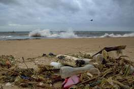 In this Aug. 13, 2015 photo, a plastic bottle lies among other debris washed ashore on the Indian Ocean beach in Uswetakeiyawa, north of Colombo, Sri Lanka. For years along the Cornish coast of Britain, Atlantic Ocean currents have carried thousands of Lego pieces onto the beaches. In Kenya, cheap flip-flop sandals are churned relentlessly in the Indian Ocean surf, until finally being spit out onto the sand. In Bangladesh, fishermen are haunted by floating corpses that the Bay of Bengal sometimes puts in their path. And now, perhaps, the oceans have revealed something else: parts of Malaysian Airlines Flight 370, the jetliner that vanished 17 months ago with 239 people on board. (AP Photo/Gemunu Amarasinghe)