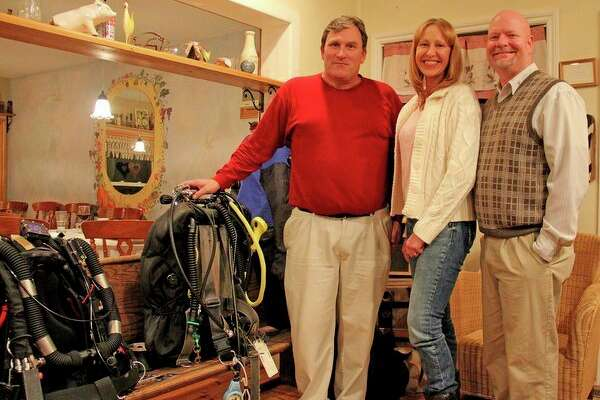 From left, Chris Roth, Cindy Lynch and Mike Lynch pose with some of their scuba gear at 'Under the Thumb,' a shipwreck history dinner hosted Saturday night by The Farm Restaurant. (Mike Gallagher/Huron Daily Tribune)