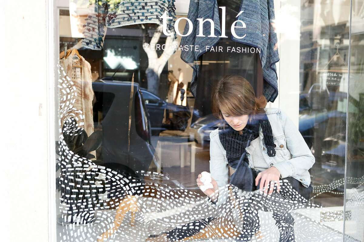 Designer and founder of Tonl� Rachel Faller, wipes down the display window at Tonle's pop up location on Thursday, January 3, 2019 in San Francisco, Calif. Tonl� is a zero-waste, fair trade women's clothing company.