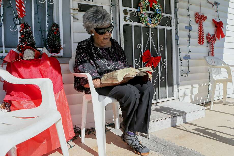 Dorothy Mondine reads the Bible on the front porch of her East Side home on Martin Luther King Jr. Drive. on Saturday, Jan. 12, 2019. Photo: Marvin Pfeiffer /Staff Photographer / Express-News 2019