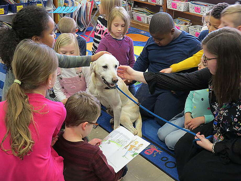 Loretta the dog came to visit students and Trinity Lutheran School Monday. Here, she meets with first-graders in Megan Langendorf's class. Photo: Carol Arnett | For The Intelligencer