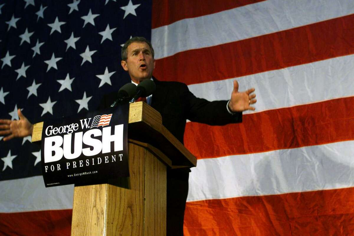 Then Texas Governor George W. Bush gestures to his supporters at a rally in Cedar Rapids, Iowa during the 2000 presidential campaign.
