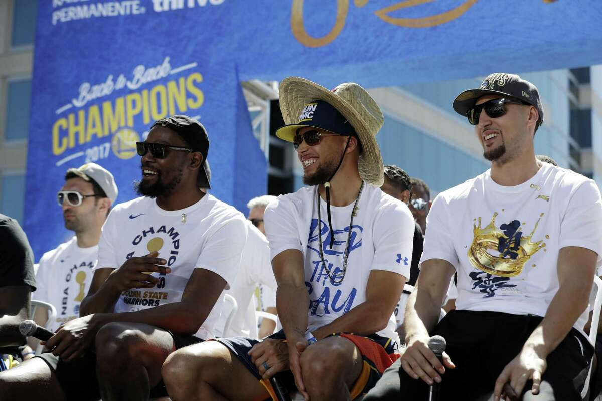 Golden State Warriors' Kevin Durant, left, Stephen Curry, center, and Klay Thompson smiles during a parade after winning the NBA basketball championship Tuesday, June 12, 2018, in Oakland, Calif. (AP Photo/Marcio Jose Sanchez)