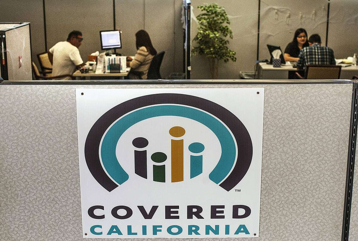 FILE - In this Nov. 1, 2016 file photo, agents help sign people up for insurance through the Covered California exchange at their storefront on Beach Boulevard in Huntington Beach, Calif. California Gov. Gavin Newsom is preparing to release his first state budget, offering his clearest outline yet of his plan to significantly boost spending on services for children including healthcare while maintaining his promise to be fiscally prudent. Newsom plans to discuss his proposal during a news conference in Sacramento on Thursday, Jan. 10, 2019. (Nick Agro/The Orange County Register/SCNG via AP, File)