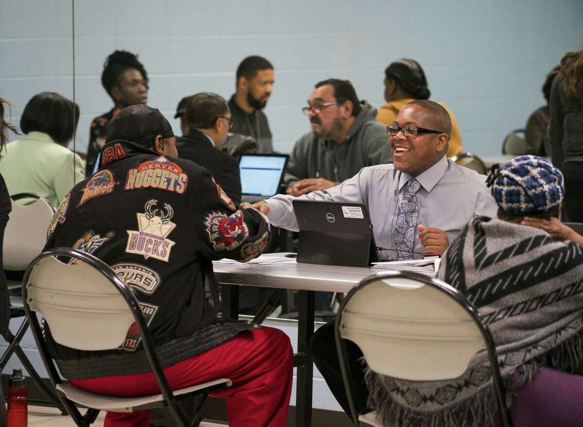 Isaac George, right, an intake specialist, greets a client applying for Harvey recovery help at a new City of Houston Housing Recovery Center set up at the North Wayside Sports and Recreation Center on N. Wayside Drive, Monday, Jan. 14, 2019. The city opened four regional centers where people can apply for Harvey relief. A fifth center is planned to open in a more central location.
