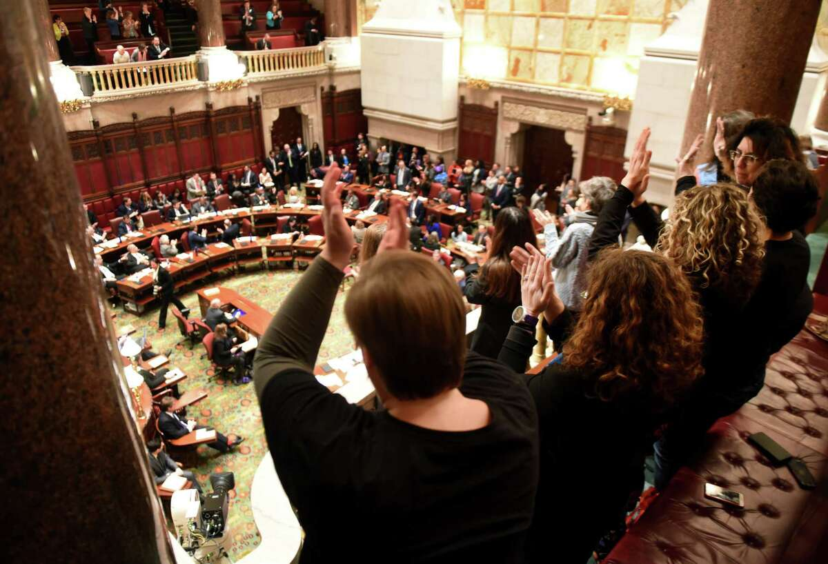 Voter rights advocates applaud the passage of senate legislation that would allow early voting on Monday, Jan. 14, 2019, in the Senate Chamber at the Capitol in Albany, N.Y. (Will Waldron/Times Union)