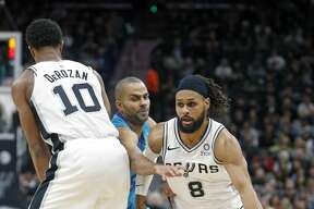 Tony Parker #9 of the Charlotte Hornets tries to get by the screen of DeMar DeRozan #10 of the San Antonio Spurs to get to Patty Mills #8 of the San Antonio Spurs on Monday, January 14, 2019 at AT&T Center.