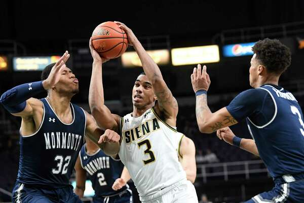 Monmouth's Diago Quinn (32) and Deion Hammond (3) defend against Siena's Manny Camper (3) during the first half of an NCAA college basketball game Tuesday, Jan. 14, 2019, in Albany, N.Y.