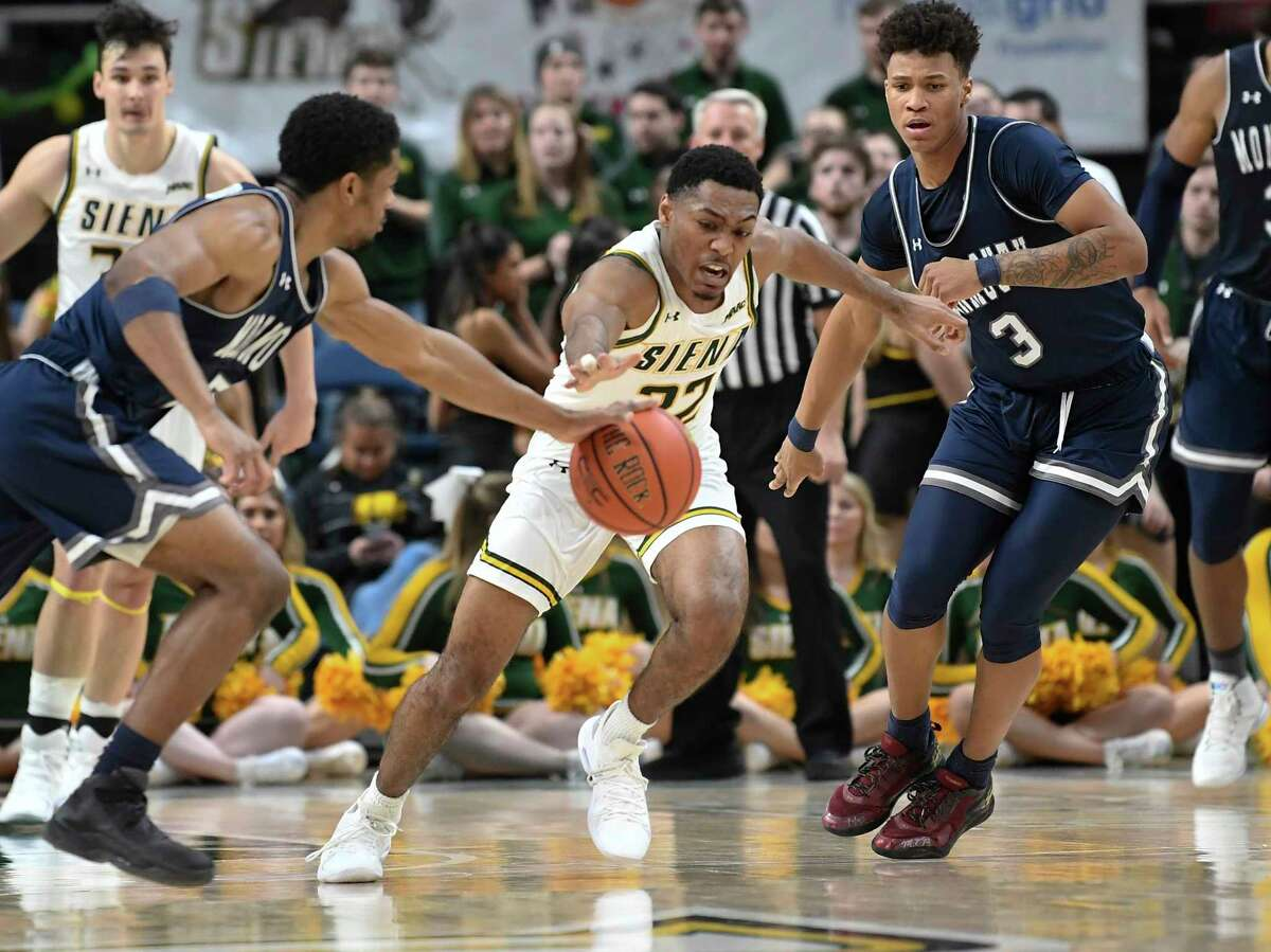 Monmouth guard Nick Rutherford (5) and teammate Monmouth guard Deion Hammond (3) chase a loose ball with Siena guard Jalen Pickett (22)during second half of an NCAA college basketball game Tuesday, Jan. 14, 2019, in Albany, N.Y. Monmouth won 63-60.