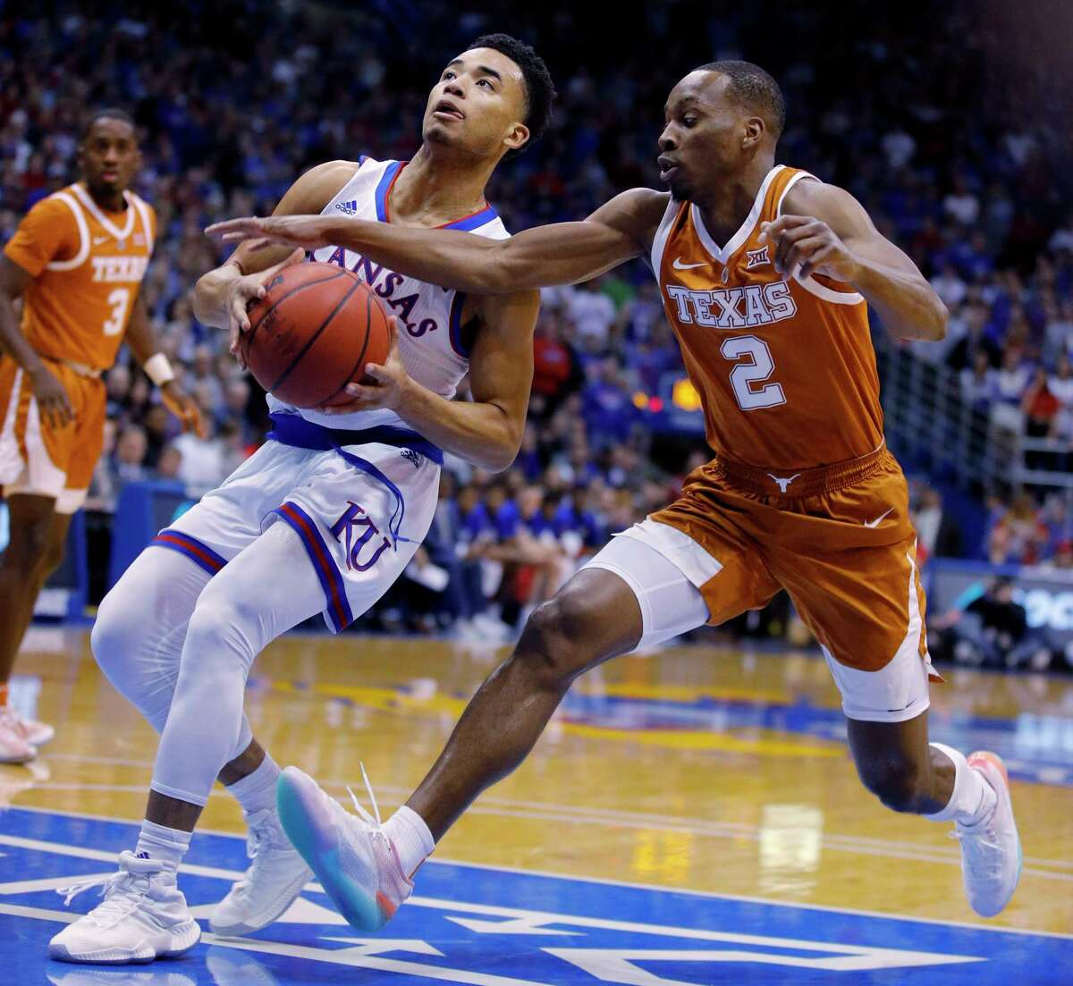 Texas guard Matt Coleman III (2) tries to steal the ball from Kansas guard Devon Dotson (11) during the first half of an NCAA college basketball game Monday, Jan. 14, 2019, in Lawrence, Kan.