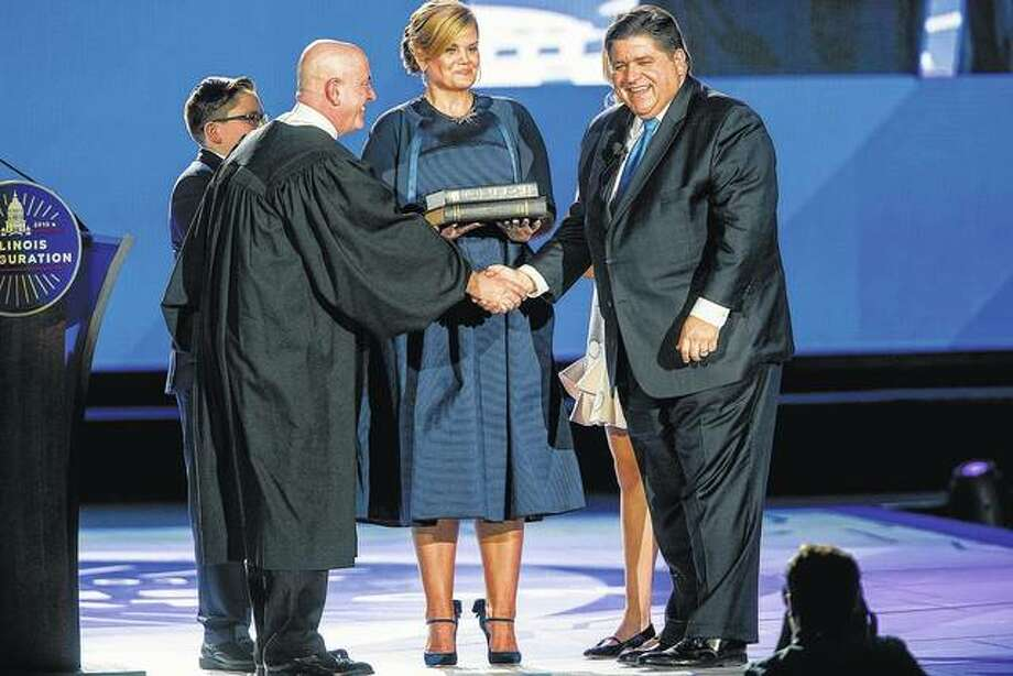 J.B. Pritzker shakes hands Monday with Judge James Snyder after taking the oath of office during inauguration ceremonies at the Bank of Springfield Center. Photo: Ted Schurter | State Journal-Register (AP)