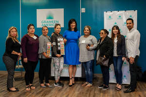 Grameen America President and CEO Andrea Jung, center, poses with staff members and some of the first Houston-area women entrepreneurs to receive microloans from the organization.