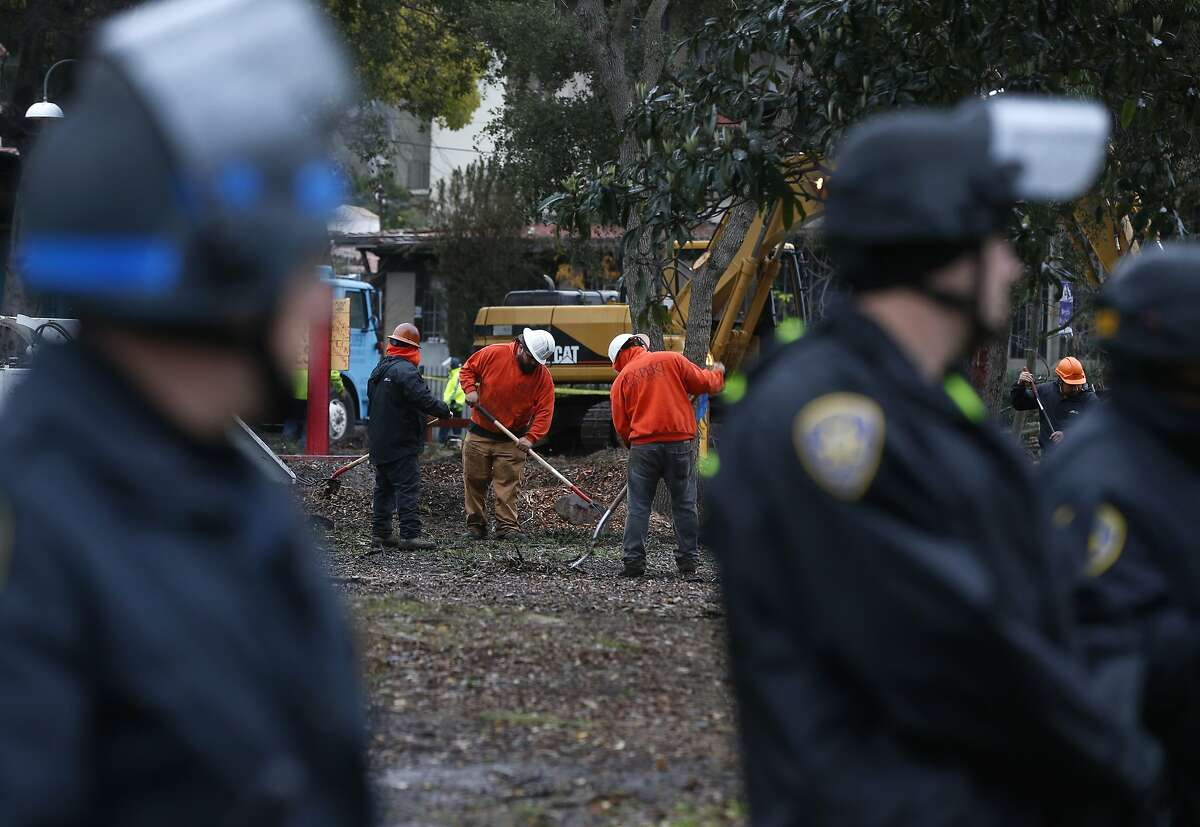 A line of police officers surround the eastern side of People's Park while a tree crew removes five trees from the park in Berkeley, Calif. on Tuesday, Jan. 15, 2019. UC Berkeley spokesman Dan Mogulof says the trees were diseased and were removed as a precaution and also to make it less attractive for camping.