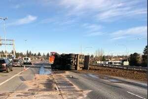 A dump truck overturned on northbound Interstate 5 near Northgate, blocking three lanes of traffic.