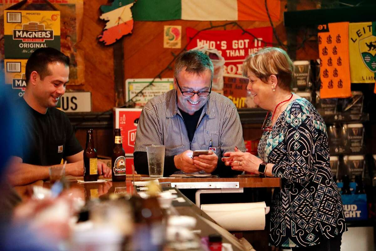 Customers Ed Brennan (center) and Bob Corriea have conversation with bar owner Annie O'Keefe at O'Keefe's in San Francisco, Calif. on Thursday, January 10, 2019.