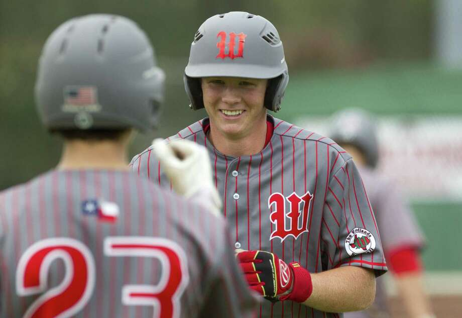 Will Swope #24 of The Woodlands smiles as he greets Drew Romo after hitting a solo home run off Keller reliever Carter Campbell (15) during the fourth inning of a high school baseball game at the Wings-N-More Classic Friday, March 10, 2017, in The Woodlands. The Woodlands defeated Keller 16-4. Photo: Jason Fochtman, Staff Photographer / Houston Chronicle / © 2017 Houston Chronicle