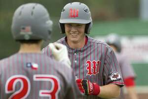 Will Swope #24 of The Woodlands smiles as he greets Drew Romo after hitting a solo home run off Keller reliever Carter Campbell (15) during the fourth inning of a high school baseball game at the Wings-N-More Classic Friday, March 10, 2017, in The Woodlands. The Woodlands defeated Keller 16-4.