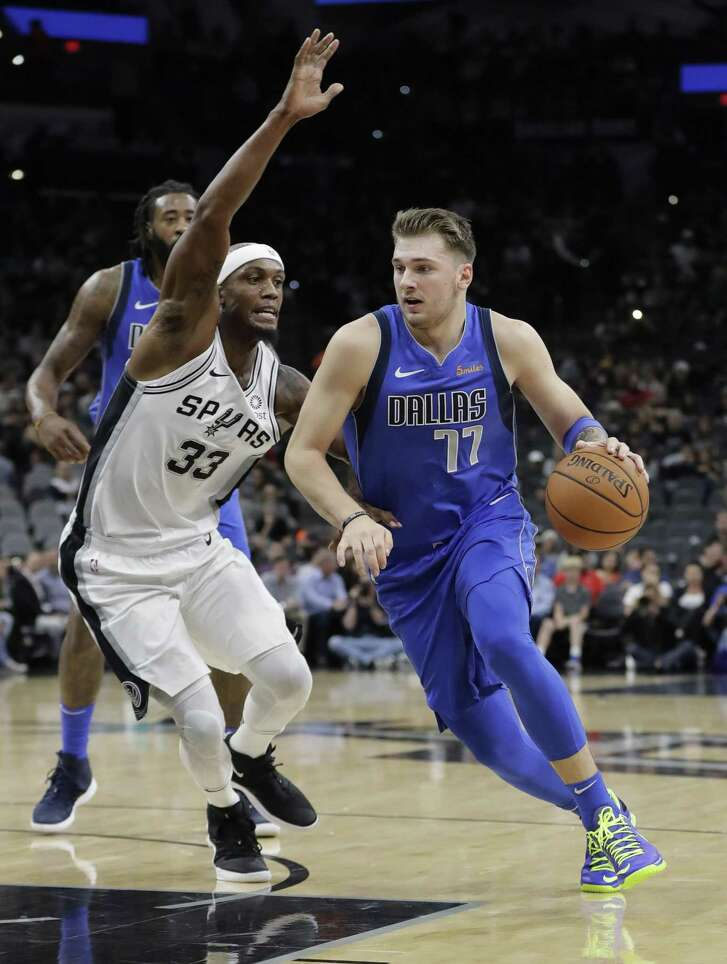 Dallas Mavericks forward Luka Doncic (77) drives around San Antonio Spurs forward Dante Cunningham (33) during the first half of an NBA basketball game, Monday, Oct. 29, 2018, in San Antonio. (AP Photo/Eric Gay)