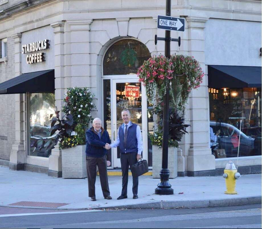 Joel Adelman, left, the former owner of 301 Greenwich Ave., shakes hands outside the building with Stephen Westerberg, of Marcus & Millichap, who brokered the $7 million sale of the property. Photo: Contributed Photo