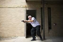 John Igoe, a member of the Citizens Police Academy, takes aim at an officer in a domestic violence scenario during a training session for potential SWAT members Aug. 18, 2015, at the Humble Police Department.