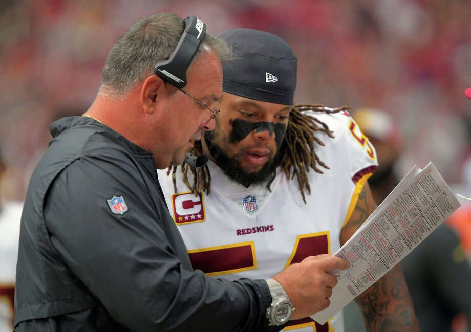 Redskins defensive coordinator Greg Manusky talks things over with linebacker Mason Foster. Photo: Washington Post Photo By John McDonnell / The Washington Post