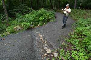 Norwalk River Valley Trail Executive Director Charlie Taney, stops and photographs some erosion on the Norwalk River Valley Trail along the Wilton Loop portion in July in Wilton.