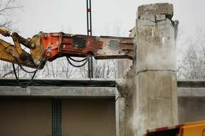 The remaining pieces of the old M-20 bridge are torn down on Monday, Jan. 14, 2019 in downtown Midland. The newly constructed westbound side is currently divided into two lanes, allowing traffic to flow both east and west while construction continues on the other half of the bridge. (Katy Kildee/kkildee@mdn.net)