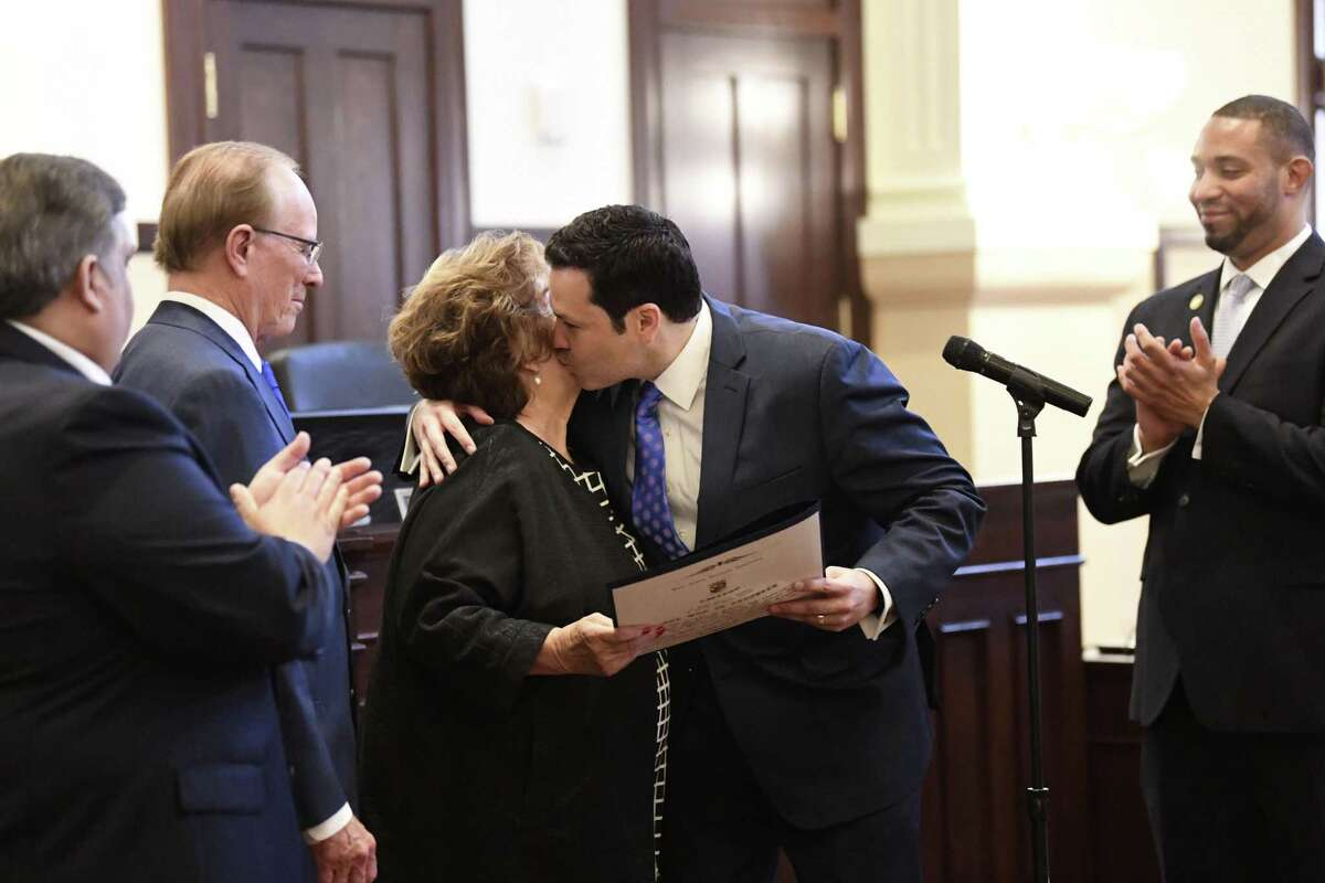 """New Bexar County Commissioner Justin Rodriguez kisses Irene Elizondo, the widow of Commissioner Paul Elizondo, who recently passed away, during the first Bexar County Commissioners Court meeting of the year on Tuesday, Jan. 15, 2019. Rodriguez is replacing Elizondo. Commissioner Sergio """"Chico"""" Rodriguez, left, County Judge Nelson Wolff, and commissioner Tommy Calvert, right, look on."""