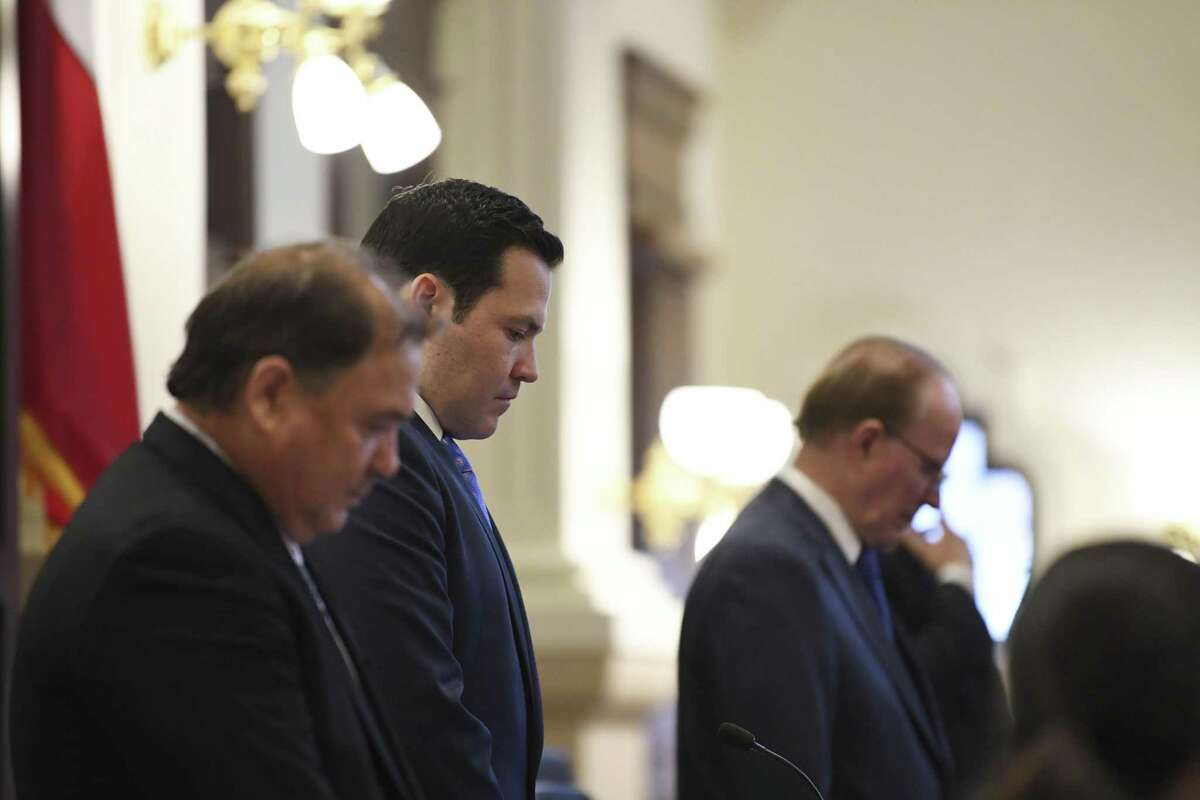 """New County Commissioner Justin Rodriguez, second from left, joins fellow commissioner Sergio """"Chico"""" Rodriguez, left, and County Judge Nelson Wolff during a prayer given by Archbishop Gustavo Garcia-Siller during the first Bexar County Commissioners Court meeting of the year on Tuesday, Jan. 15, 2019. Rodriguez replaced long-time commissioner Paul Elizondo, who recently died."""