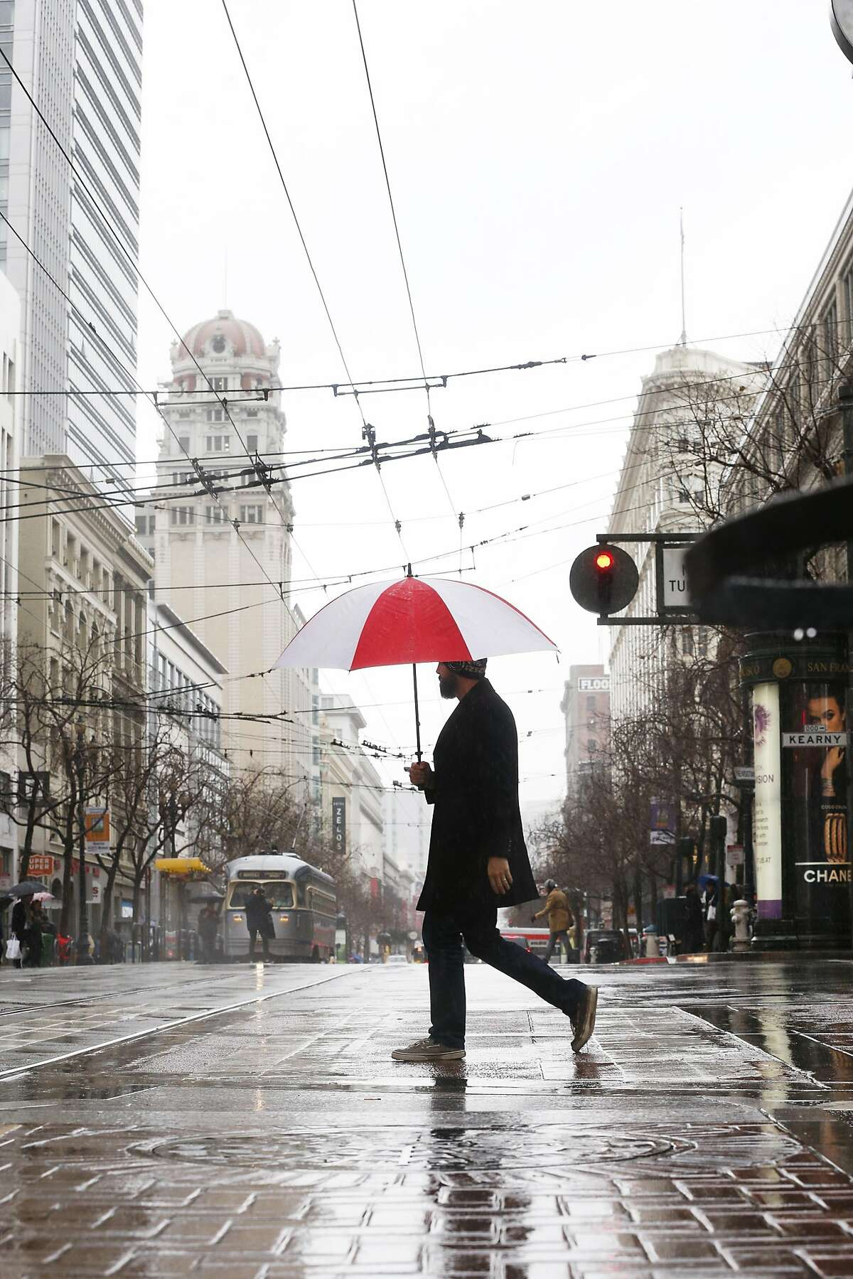 Daniel Sisson of San Francisco stays dry under his umbrella as he crosses Market Street to get some lunch on Tuesday, January 15, 2019 in San Francisco, Calif.