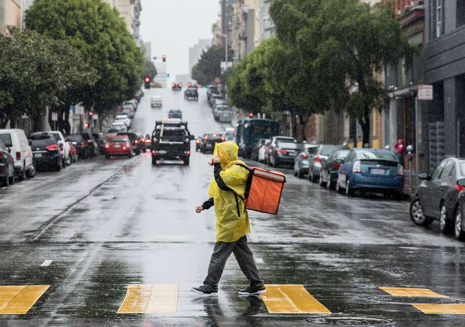 A food delivery worker sports a bright yellow poncho during rainy weather in San Francisco, Calif. Tuesday, Jan. 15, 2019. Photo: Jessica Christian, The Chronicle