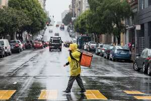 A food delivery worker sports a bright yellow poncho during rainy weather in San Francisco, Calif. Tuesday, Jan. 15, 2019.
