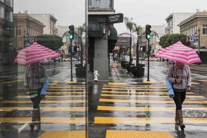 A woman carries a yoga mat and an umbrella while making her way down Polk Street during a rainstorm in San Francisco, Calif. Tuesday, Jan. 15, 2019.