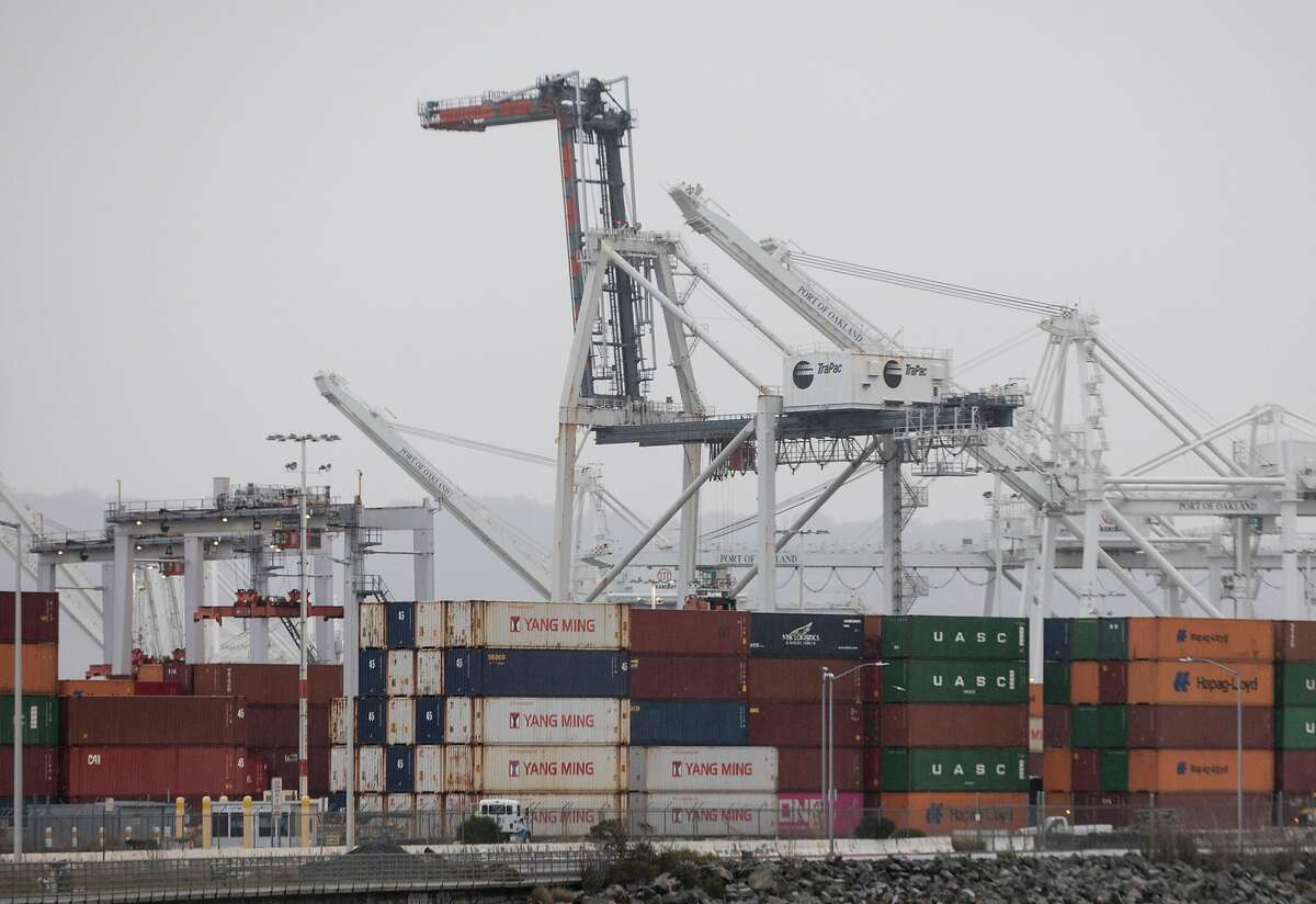 Large cranes work to remove shipping containers from incoming ships at the Port of Oakland in Oakland, Calif. Tuesday, Jan. 15, 2019.