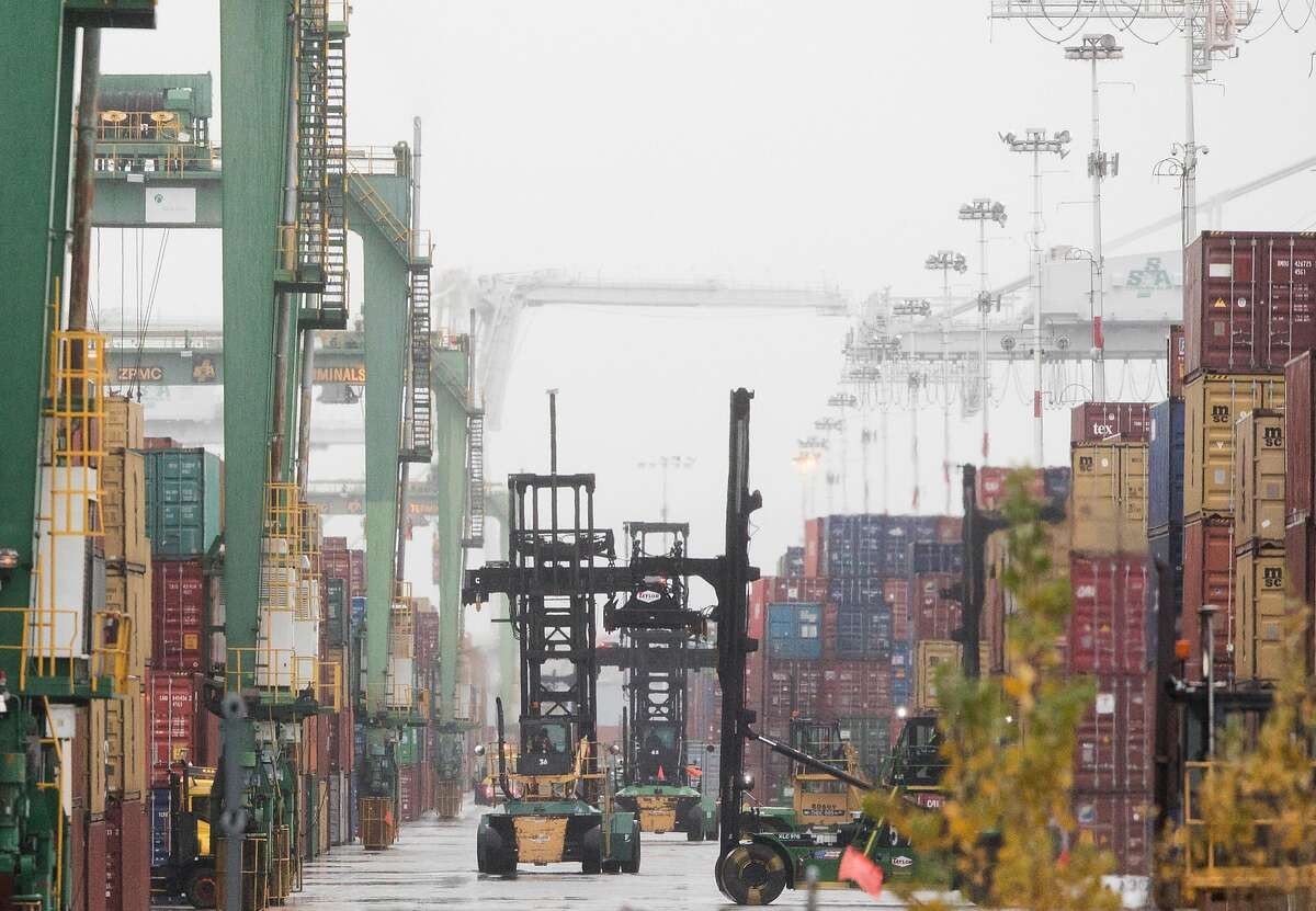 Tractors move through the yard and work to move shipping containers scheduled for departure at the Port of Oakland in Oakland, Calif. Tuesday, Jan. 15, 2019.