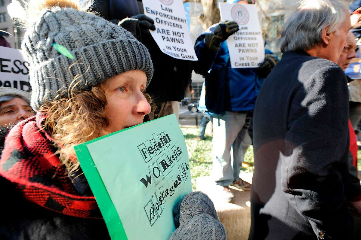 A protester holds her sign close to her face as Senator Ed Markey (D-MA) addresses a protest rally by government workers and concerned citizens against the government shutdown on Friday, January 11, 2019 at Post Office Square near the Federal building, headquarters for the EPA and IRS in Boston. - The rally was organized by The American Federation of Government Employees (AFGE). New England has 516 EPA employees that is now down to a staff of 22. (Photo by Joseph PREZIOSO / AFP)JOSEPH PREZIOSO/AFP/Getty Images
