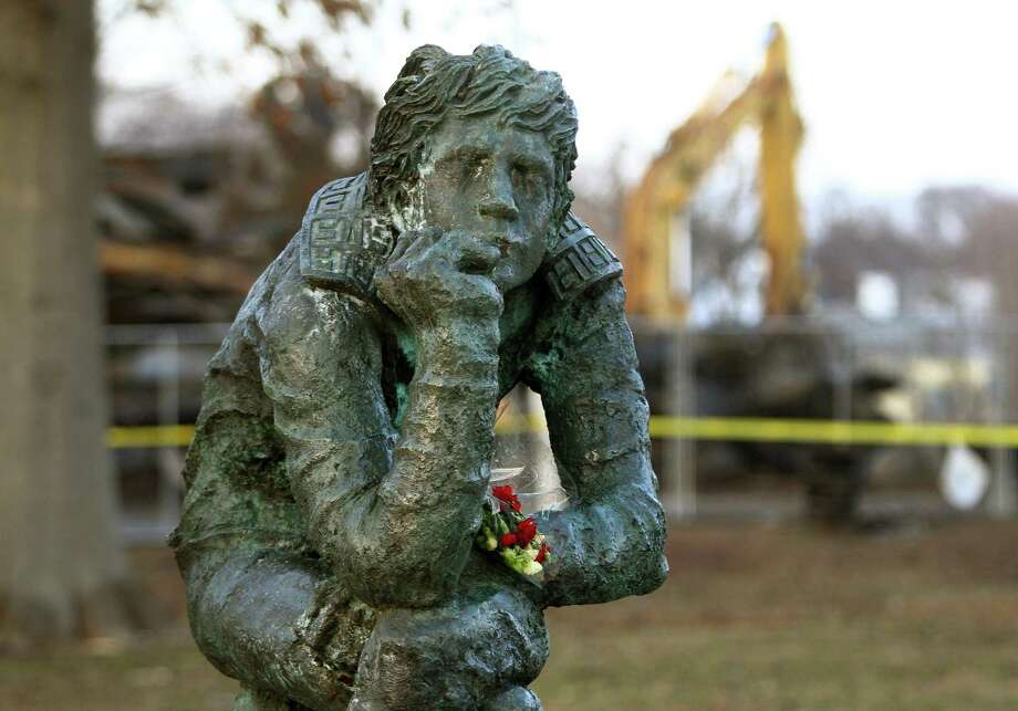 Flowers were left as a memorial on a nearby statue during clean-up after a fire destroyed the old theater at American Shakespeare State Park in Stratford. Photo: Christian Abraham / Hearst Connecticut Media / Connecticut Post