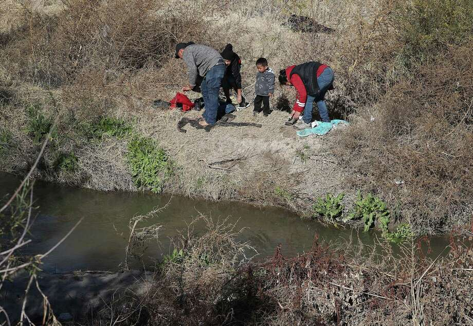 A man from Honduras and a woman and her children from Guatemala change into dry clothes as they prepare to turn themselves over to the Border Patrol after crossing the Rio Grande  in El Paso. A reader notes that immigrants are not afraid to cross the border. Photo: Joe Raedle / Getty Images / 2019 Getty Images