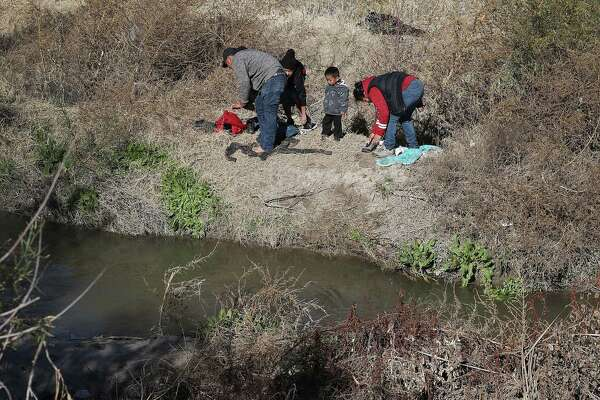 A man from Honduras and a woman and her children from Guatemala change into dry clothes as they prepare to turn themselves over to the Border Patrol after crossing the Rio Grande in El Paso. A reader notes that immigrants are not afraid to cross the border.