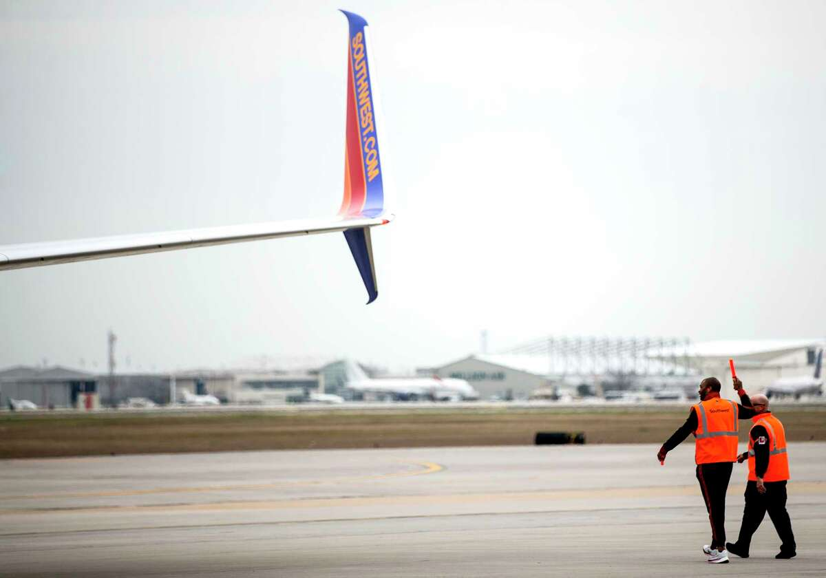 Houston Rockets forward PJ Tucker helps guide a Southwest jet from the gate at William P. Hobby Airport on Tuesday, Jan. 15, 2019, in Houston. The Rockets players teamed up with Southwest Airlines to surprise travelers at Hobby Airport. Southwest employees joined the players, Clutch the Bear, and members of the Rockets Power Dancers in greeting and interacting with customers at the airport while helping to perform duties such as announcing flight information and collecting boarding passes.