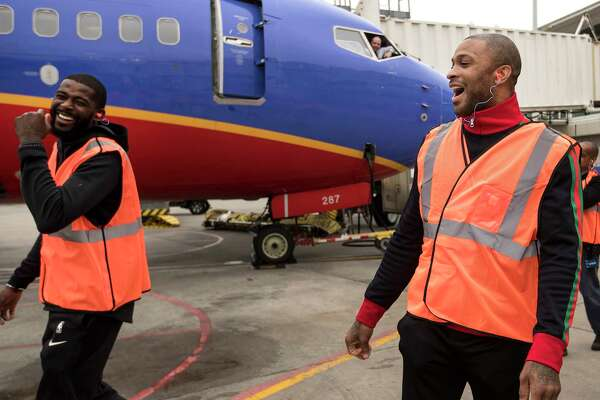 Houston Rockets players James Ennis III, left, and PJ Tucker walk into the ramp area at William P. Hobby Airport on Tuesday, Jan. 15, 2019, in Houston. The Rockets players teamed up with Southwest Airlines to surprise travelers at Hobby Airport. Southwest employees joined the players, Clutch the Bear, and members of the Rockets Power Dancers in greeting and interacting with customers at the airport while helping to perform duties such as announcing flight information and collecting boarding passes.