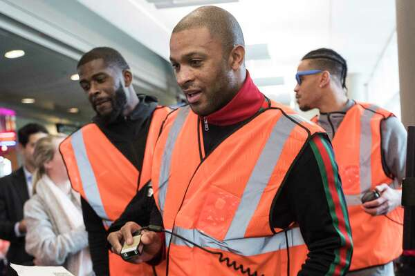 Houston Rockets forward PJ Tucker, center, scans boarding passes for passengers boarding a Southwest Airlines jet bound of St. Louis at William P. Hobby Airport on Tuesday, Jan. 15, 2019, in Houston. The Rockets players teamed up with Southwest Airlines to surprise travelers at Hobby Airport. Southwest employees joined the players, Clutch the Bear, and members of the Rockets Power Dancers in greeting and interacting with customers at the airport while helping to perform duties such as announcing flight information and collecting boarding passes. Rockets teammates James Ennis III, left, and Gerald Green are shown in the background.