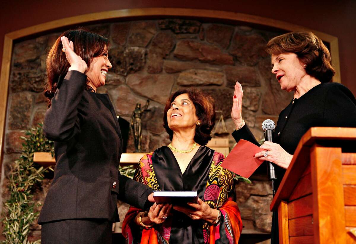 District Attorney Kamala Harris (left) is sworn in by US Senator Dianne Feinstein (right). In the center is Kamals's mom Shymala Harris. District Attorney Kamala Harris is sworn in to a second term in office after garnering more than 98% of the vote in the first uncontested race for District Attorney of San Francisco since 1991. US Senator Dianne Feinstein administered the oath of office. Ceremony took place at fhe Delancey Street Town Hall. Photo taken on 1/8/08 in San Francisco, CA. Photo by Michael Maloney / San Francisco Chronicle ***Kamala Harris, Dianne Feinstein, Shymala Harris, Gavin Newsom, Willie Brown