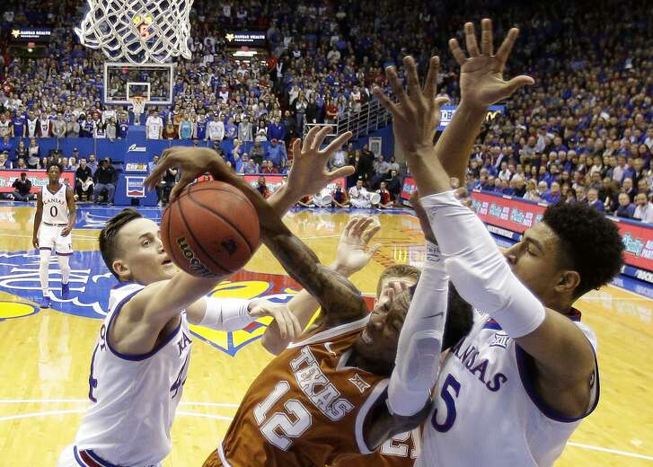 Texas guard Kerwin Roach II (12) battles for a rebound with Kansas forward Mitch Lightfoot (44) and guard Quentin Grimes (5) during the first half of an NCAA college basketball game Monday, Jan. 14, 2019, in Lawrence, Kan. (AP Photo/Charlie Riedel)