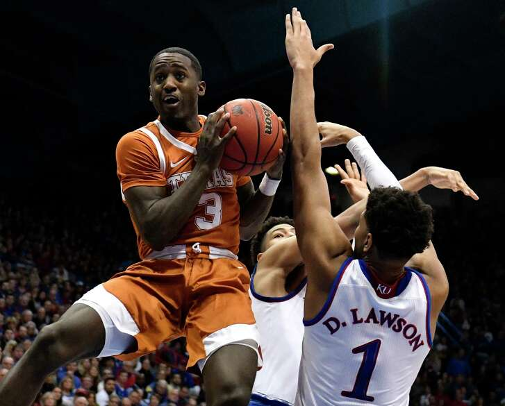 LAWRENCE, KANSAS - JANUARY 14: Courtney Ramey #3 of the Texas Longhorns goes to the basket against Dedric Lawson #1 and Quentin Grimes #5 of the Kansas Jayhawks in the second half at Allen Fieldhouse on January 14, 2019 in Lawrence, Kansas.
