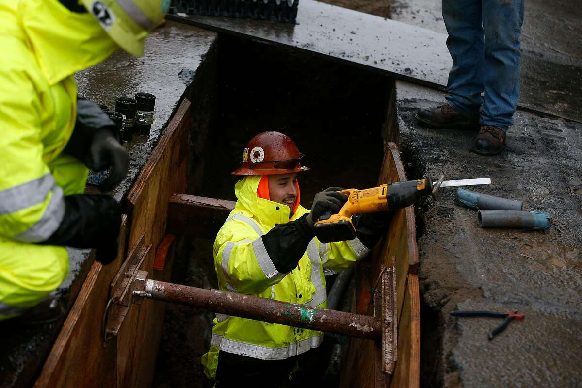 Brian Gaona with Phoenix Electric works in the ground in a closed off section of Van Ness Avenue in the rain on Tuesday, January 15, 2019 in San Francisco, Calif.