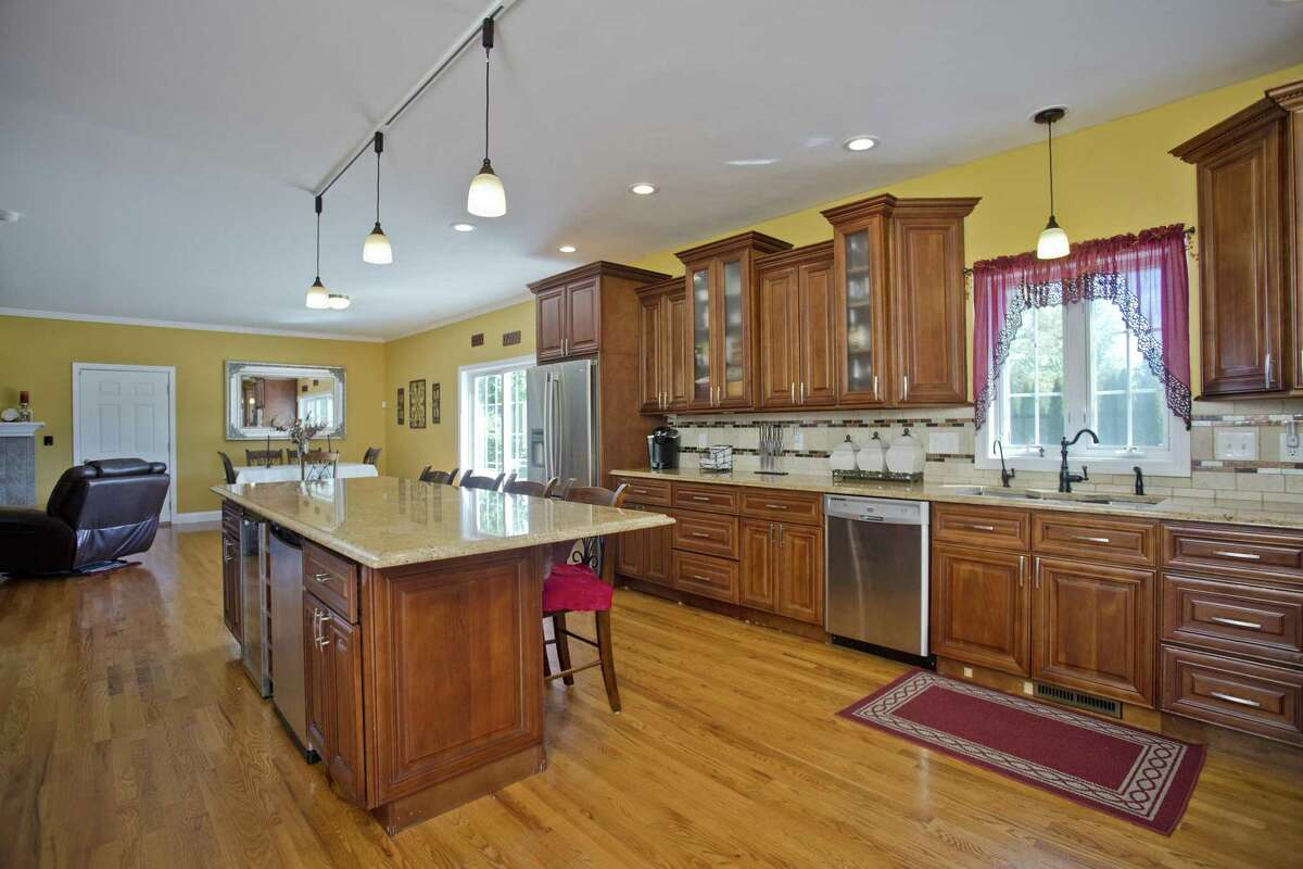 The gourmet kitchen at 246 Upper State St. in North Haven features a huge center island with granite counters and ogee edging, stainless steel appliances and handsome staggered solid wood cabinets accented with crown rope, rail and baseboard moldings.