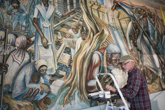 """Art restorer Scott Haskins works on the mural titled """"The Contribution of the Negro Woman in American Life and Education,"""" Monday, Jan. 14, 2019, in Houston. The mural was created by Dr. John Biggers in 1953 and is located at the Blue Triangle Community Center. The mural was severely damaged by Hurricane Harvey."""