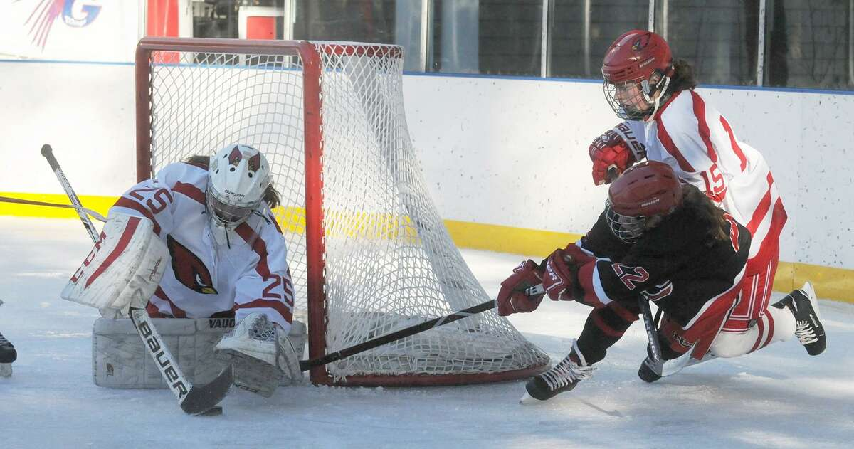 Greenwich goalie Hannah Goldenberg stops a shot by New Canaans Shea Hobbs (22) as Katie Piotrzkowski (15) defends during the Winter Classic on Dec. 29 at the Greenwich Skating Club.
